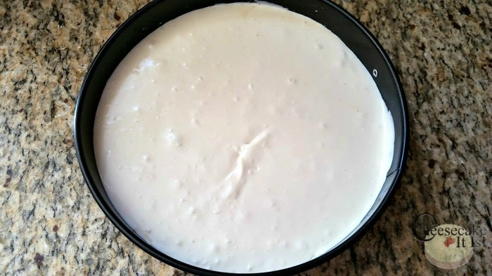 Coconut cheesecake batter poured into springform pan.