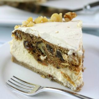 Slice of carrot cake cheesecake on a white plate with a fork. Rest of cheesecake in background.