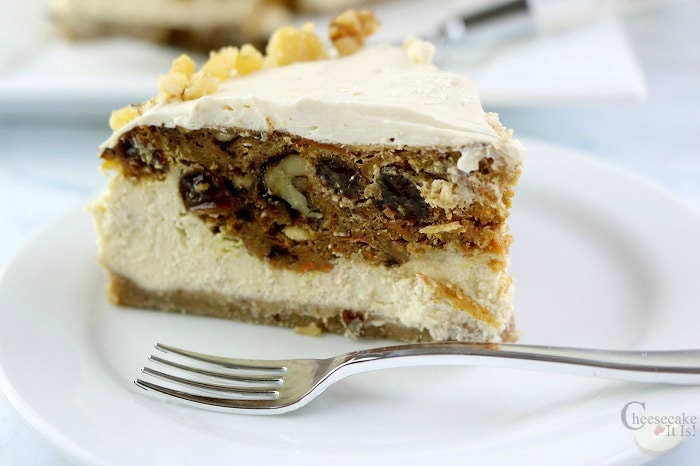 Slice of carrot cake cheesecake on a white plate with a fork.