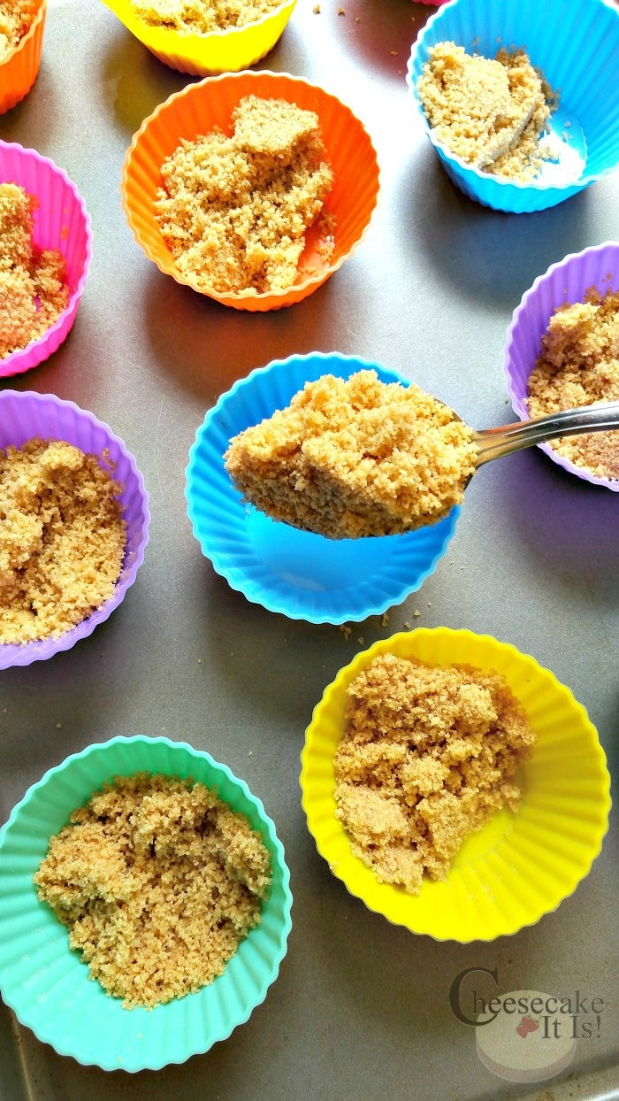 Spoon graham cracker mix into cupcake liners