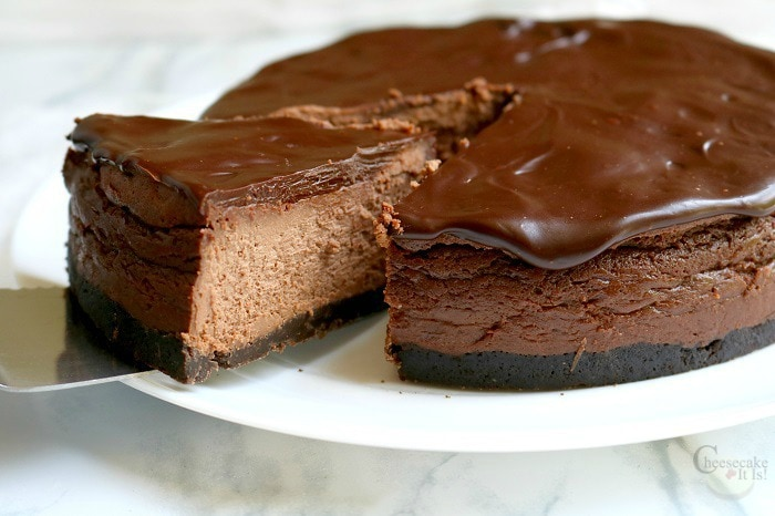 Slice of triple chocolate cheesecake being lifted out of the whole cheesecake.