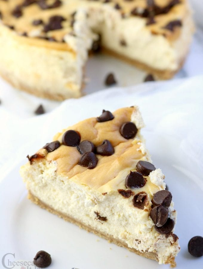 Slice of chocolate chip cheesecake on a white plate with the rest of the cheesecake in the background.