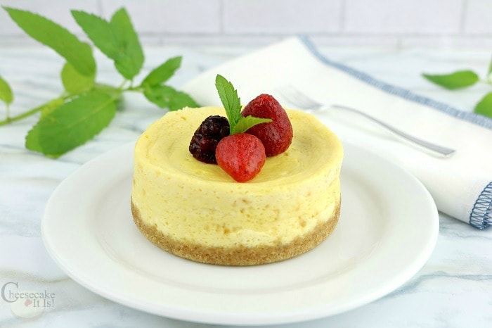 Cheesecake for one on white plate with berries on top.