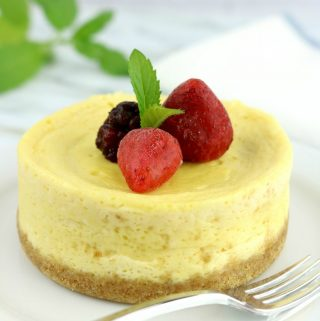 Small round microwave cheesecake for one on a white plate with berries on top.
