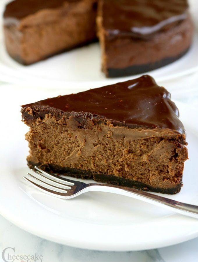 Slice of Triple Chocolate Cheesecake on a white plate with a fork. Rest of cheesecake in the background.