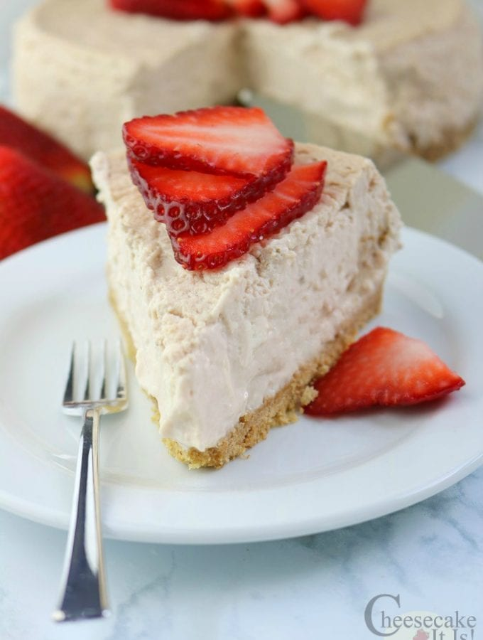 Slice of Strawberries And Cream Cheesecake on a white plate with a fork the rest of the cheesecake in background.