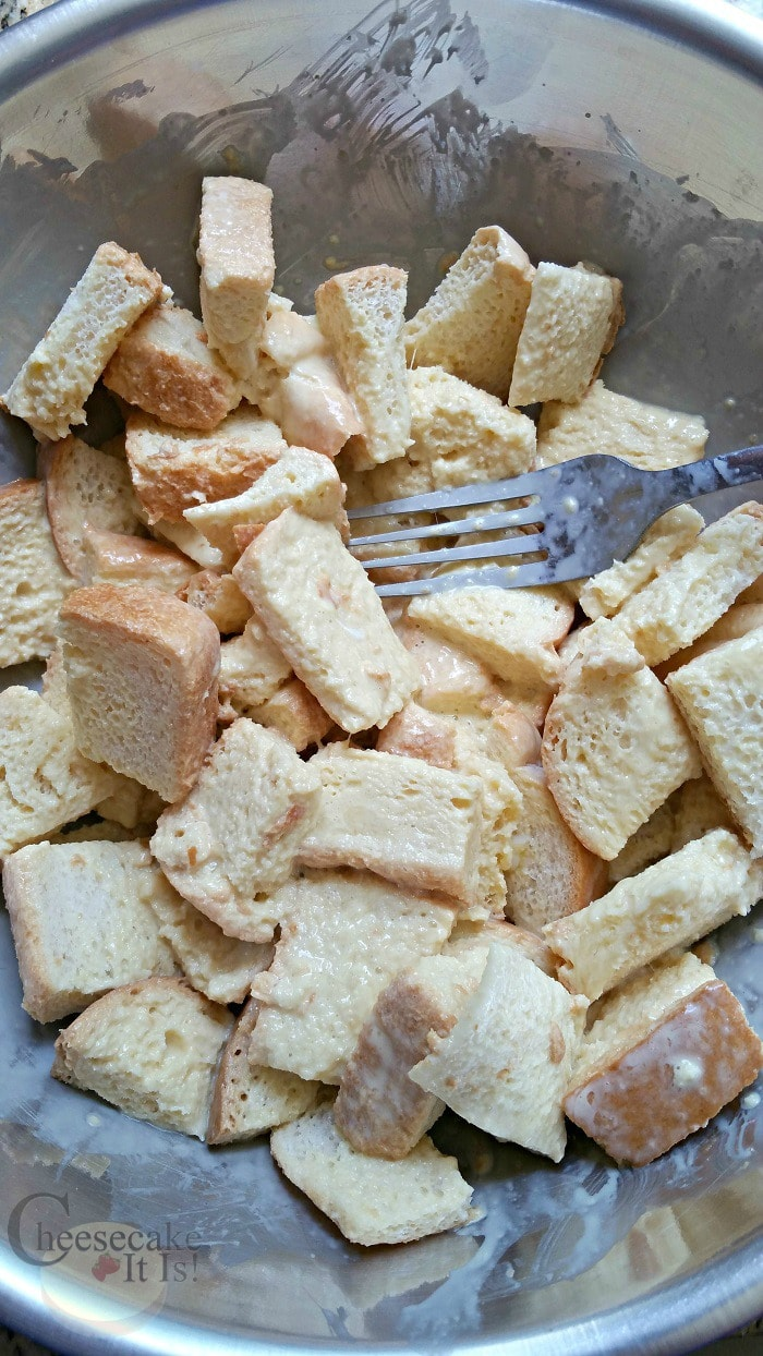 Bread chunks coated in egg mixture in bowl with fork.
