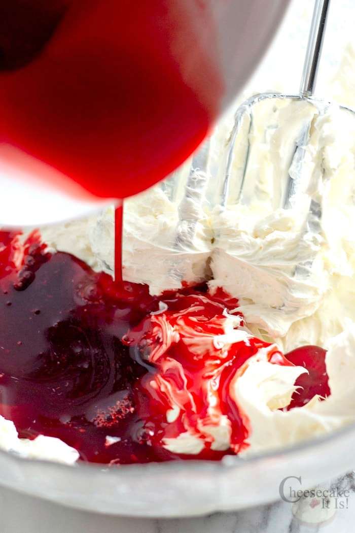 Red jello mixing being poured into cheesecake mixture.