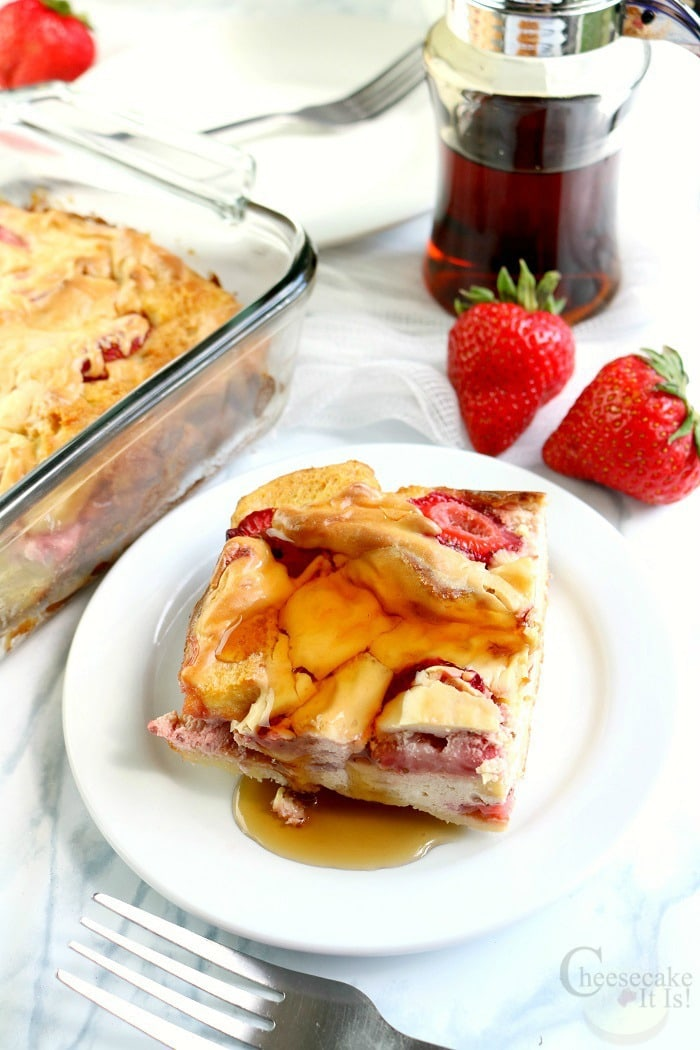 Slices of Strawberry Cheesecake French Toast Bake on white plate with syrup. Rest in background with syrup jar.