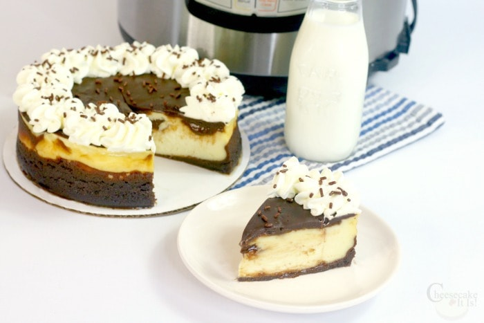 Slice of cheesecake on white plate with the rest of the cheesecake in the background and a jar of milk