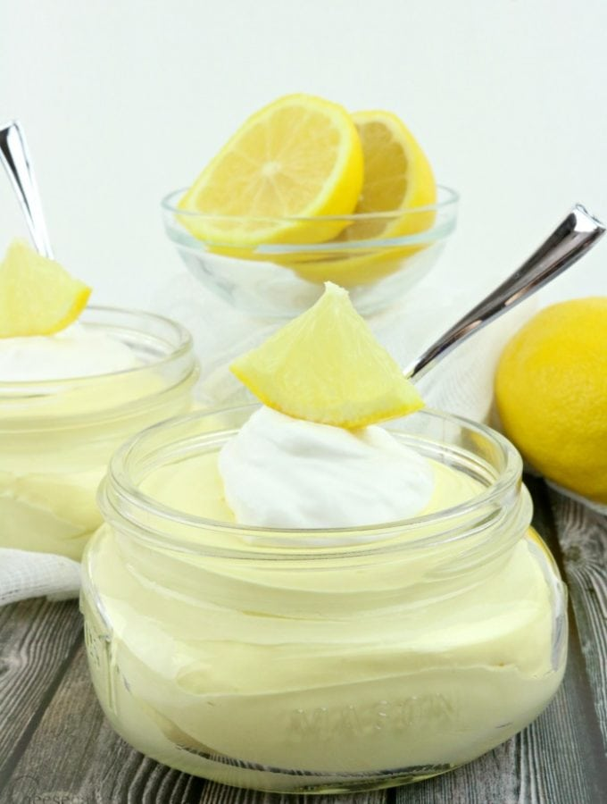 Jar of lemon cheesecake fluff topped with whipped cream and a piece of lemon. Dish of sliced lemon in background