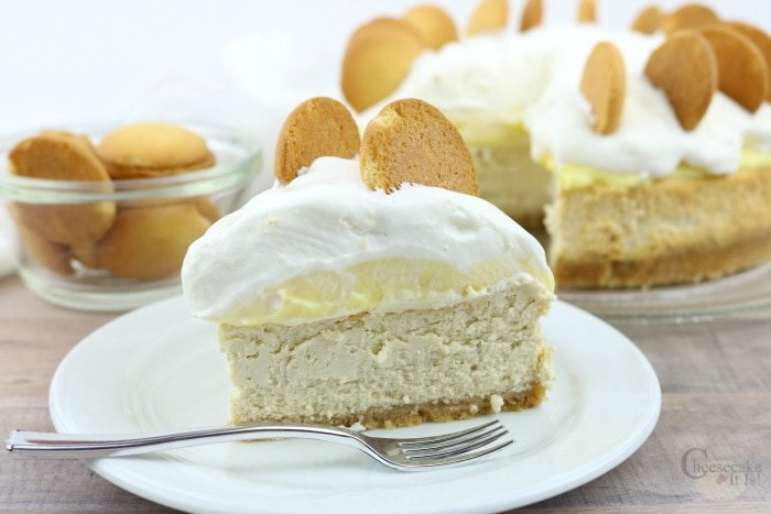 Slice of banana cheesecake on white plate with rest of cheesecake in background