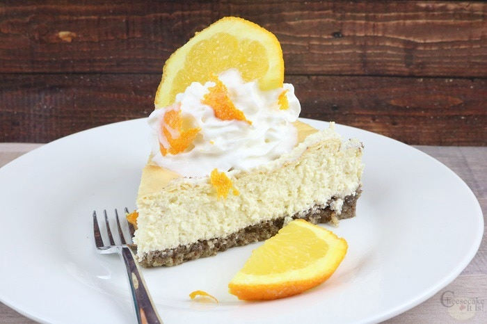 Orange cheesecake slice on white plate with orange slice and fork