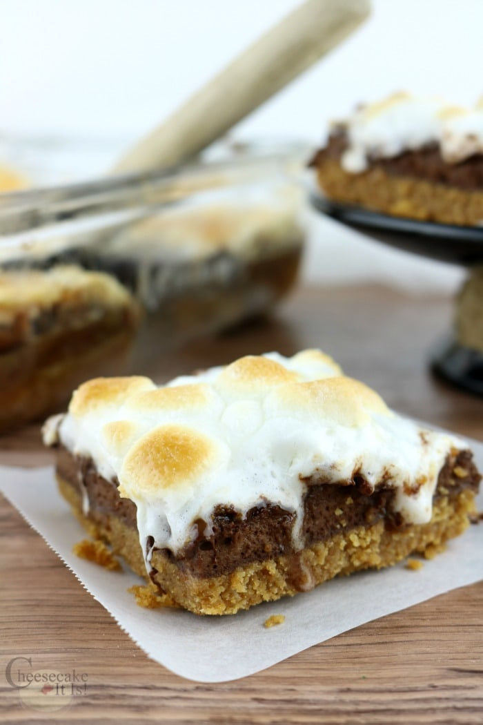 Baked S'mores cheesecake bar on wax paper with pan of bars in background
