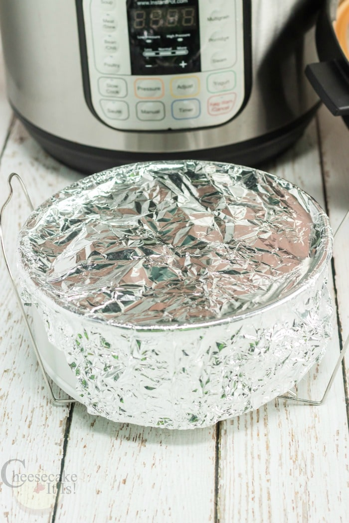 Cheesecake with foil covering top with Instant Pot in background