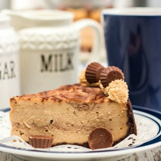 Slice of chocolate peanut butter cheesecake on white plate with blue edge blue coffee cup to right side