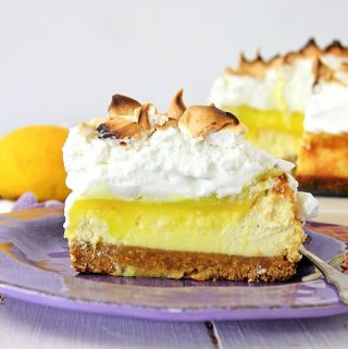 Slice of Lemon Meringue Cheesecake on a purple plate with rest of cheesecake in background