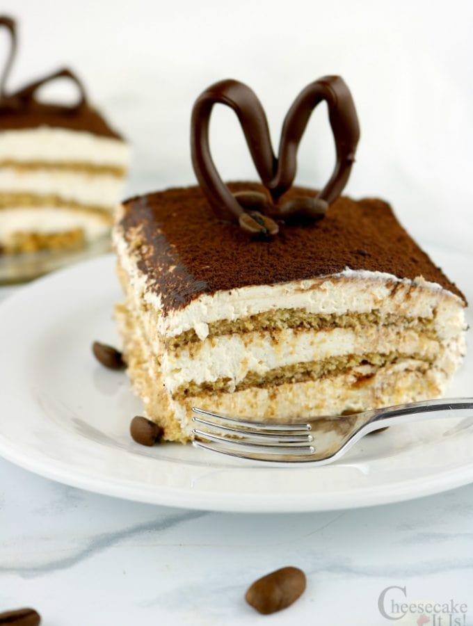 Slice of Tiramisu Cheesecake Icebox Cake on white plate with another slice in background