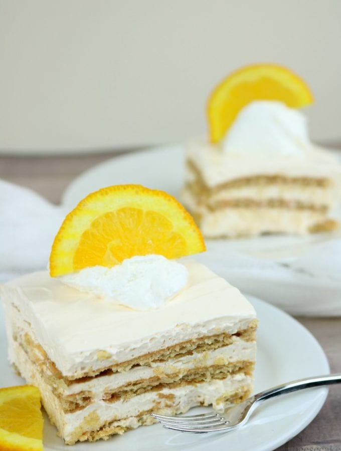 Two slices of creamsicle cheesecake icebox cake both on white plates with a half orange slice on top