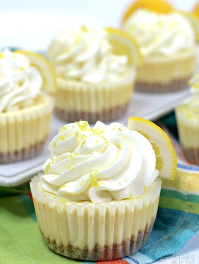 Lemon cheesecake minis in cupcake liners topped with whipped topping and lemon zest