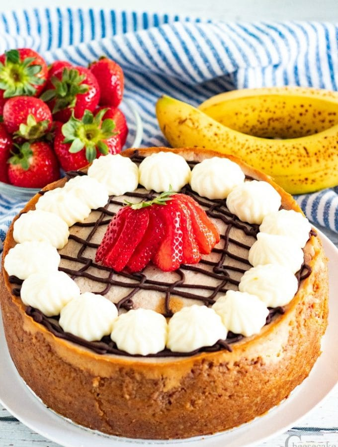 Whole banana split cheesecake on white plate with strawberries and bananas in background