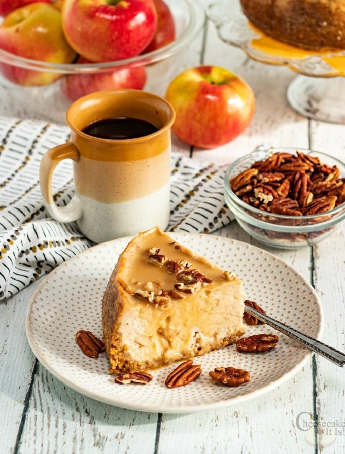 Slice of instant pot caramel apple cheesecake on white plate with coffee nuts and apples in background
