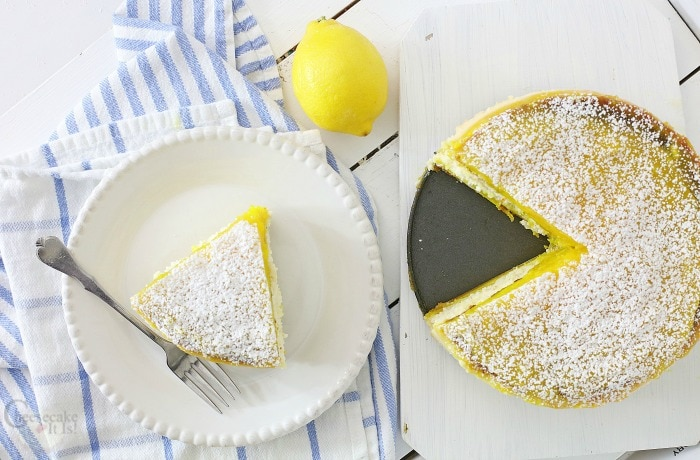 Slice of lemon bar cheesecake on white plate then rest of cheesecake to right side