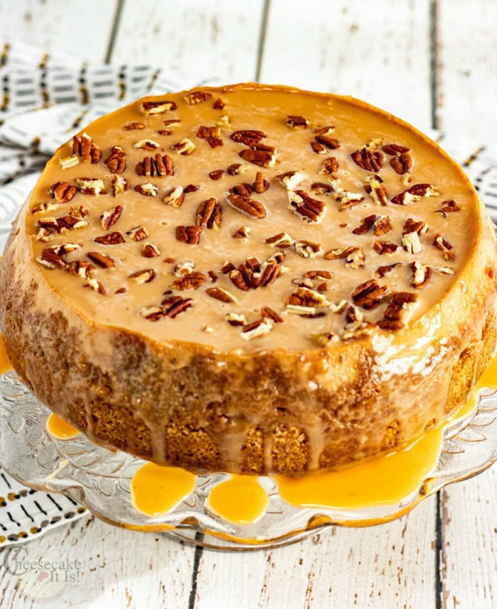 Whole caramel apple cheesecake on glass stand topped with pecans